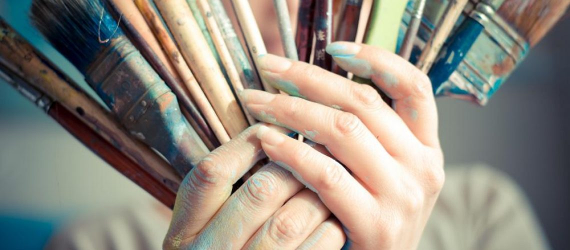 woman-holding-paint-brushes